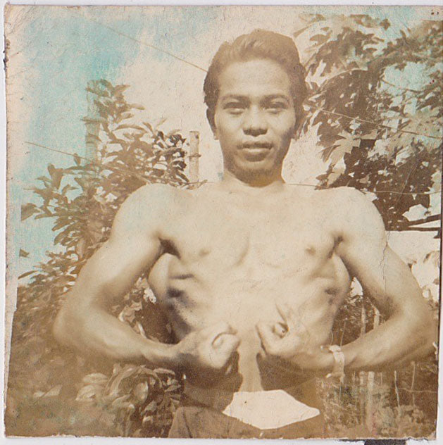 Undated hand-tinted vintage sepia photo of an Asian man flexing outdoors.