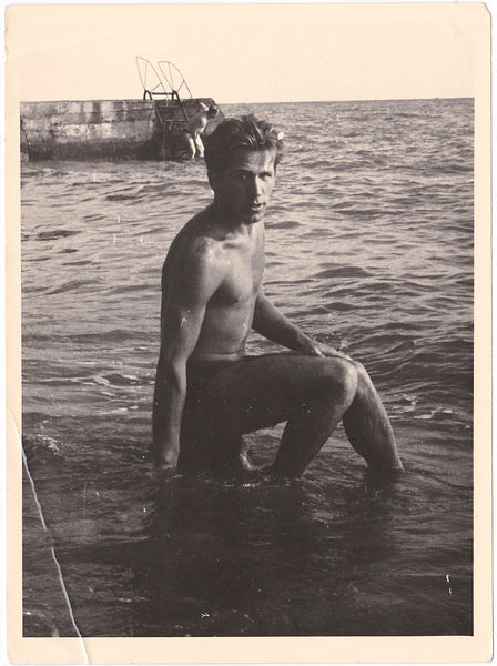 Handsome guy sits on a rock with his feet in the water. Vintage photo gloss finish, dated 1960.