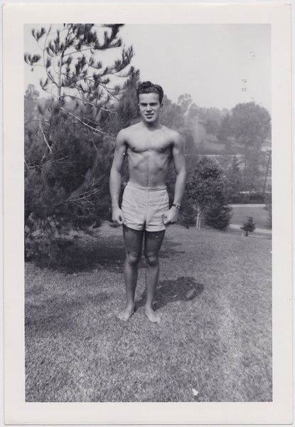 A handsome young guy stands at attention in a park-like setting vintage photo