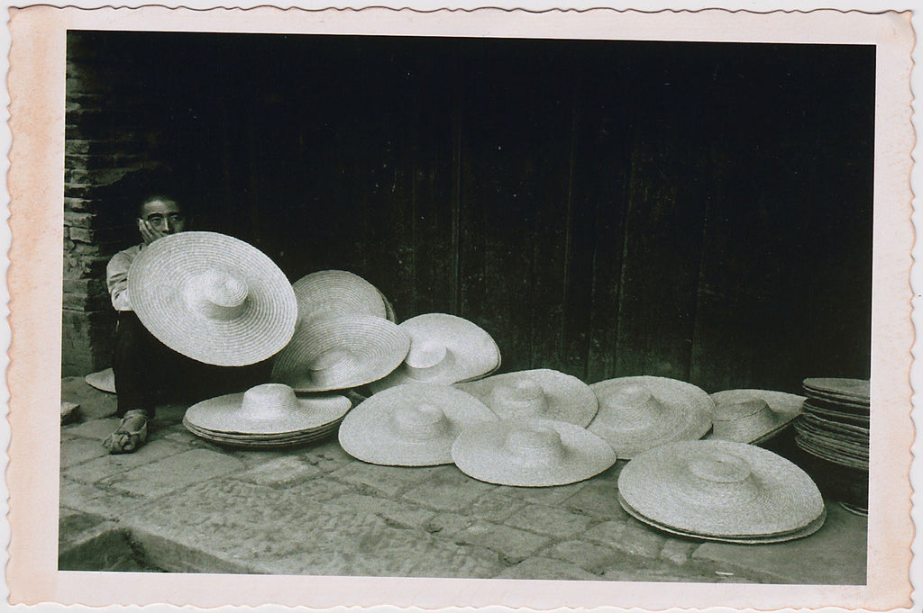 Beautifully composed image of a hat vendor almost hidden behind his large straw hats.