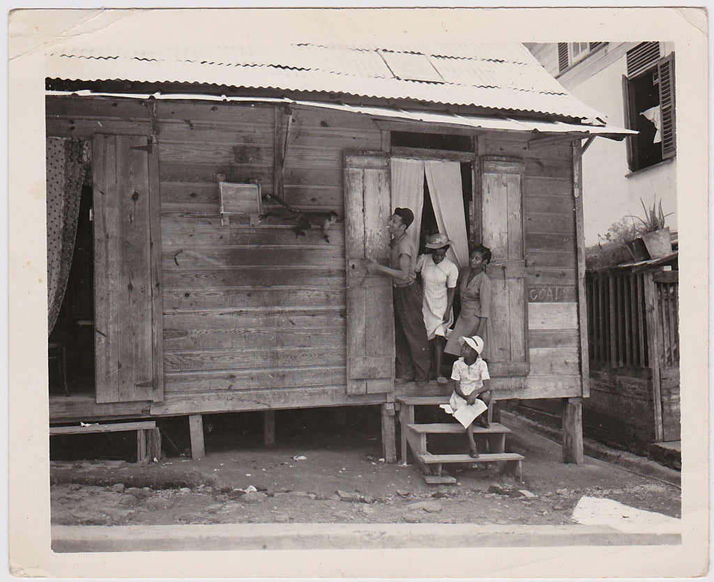 A strange image of three black women and a white man with a cigarette at the door of a simple wood house, watching a monkey climb towards them.