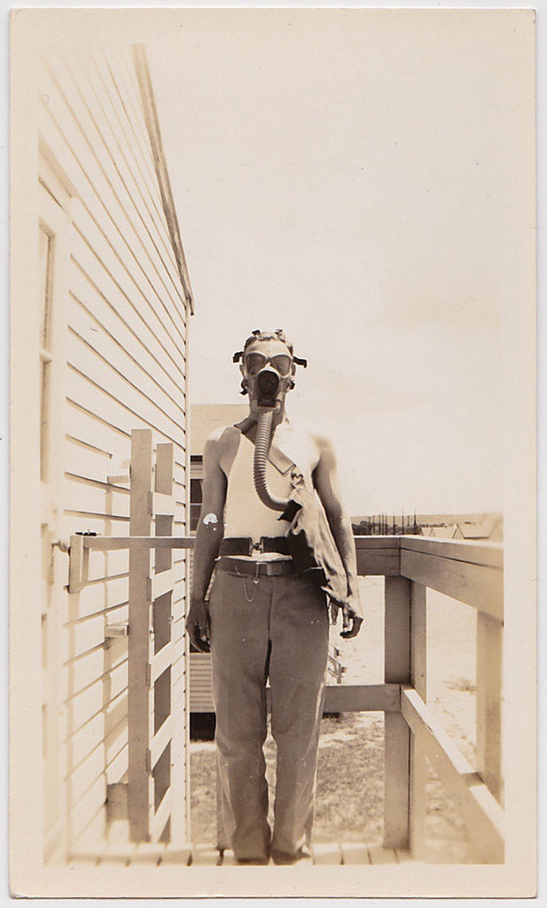 vintage sepia snapshot soldier stands in front of the barracks in a muscle t-shirt demonstrating the latest in gas mask fashion.