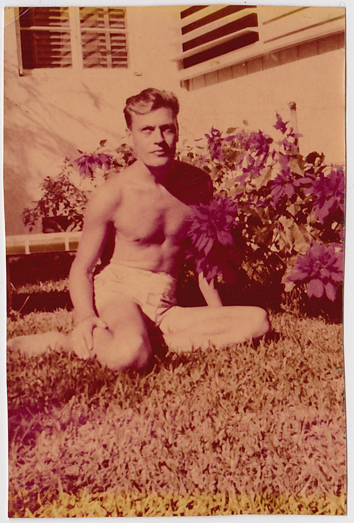 "Very early color snapshot of a handsome blond man wearing shorts, sitting on the lawn next to a bed of poinsettias. It has the golden yellow hue typical of early color photos and the je ne sais quoi that tilts ""gay."""