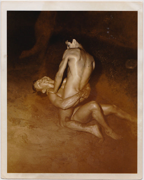 Two handsome young nude models wrestle in the sand in this rare night-time shot