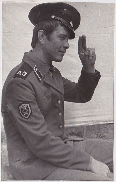 Vintage photo Handsome Russian soldier seen in profile, offering a relaxed salute.