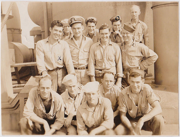 13 sailors crowd in for a group photo, seemingly relaxed and smiling.