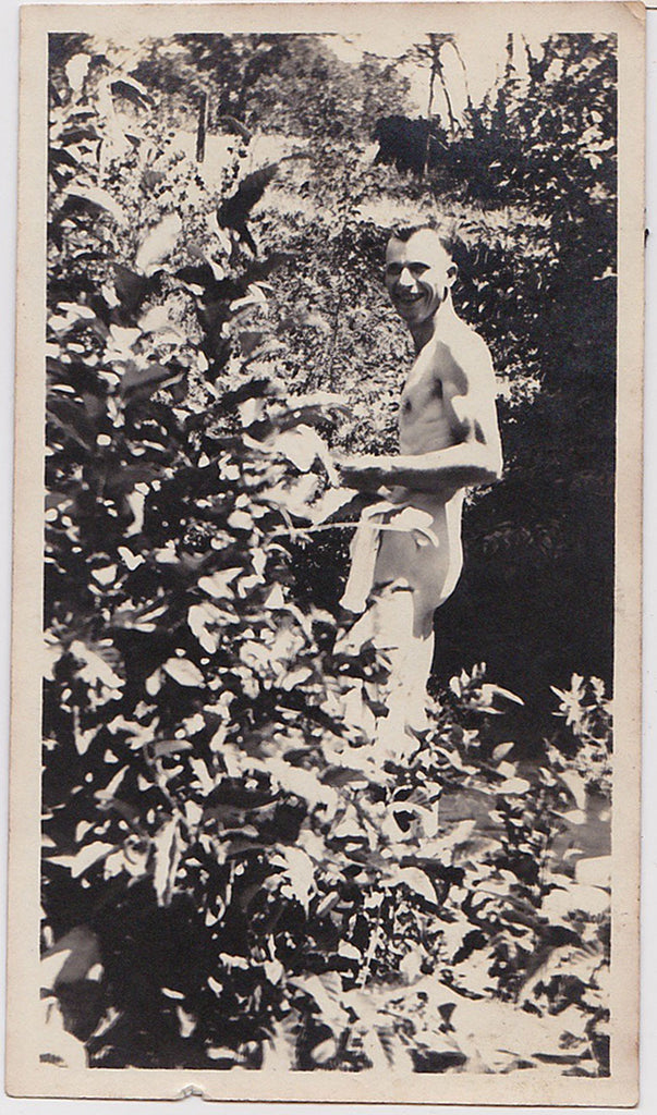 Anonymous vintage snapshot of a smiling naked man heading into the shrubbery