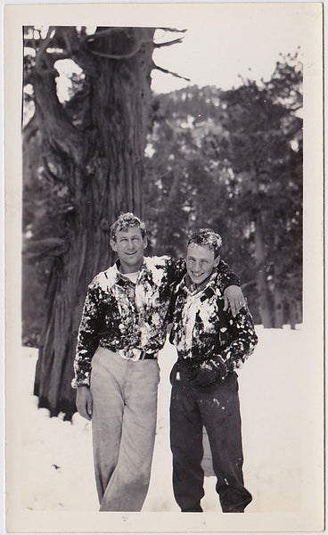 Two affectionate guys covered in snow. Vintage photo,