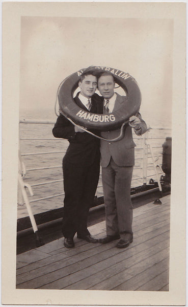 vintage snapshot Two men share a life preserver on the deck of a ship out of Hamburg.