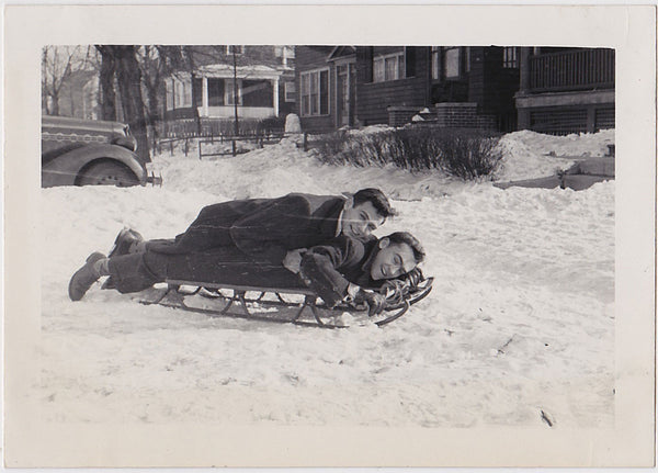 Two men share a sled. They don't seem to be going anywhere vintage snapshot 1950s.