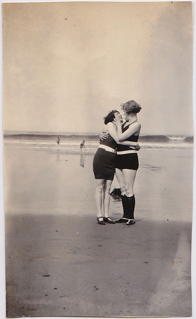 Two affectionate women share a romantic moment together on the beach, gazing into each others' eyes, vintage photo