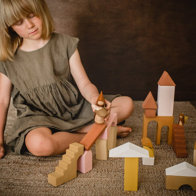 Child playing with Raduga Grez building blocks with a Sweet Elm doll