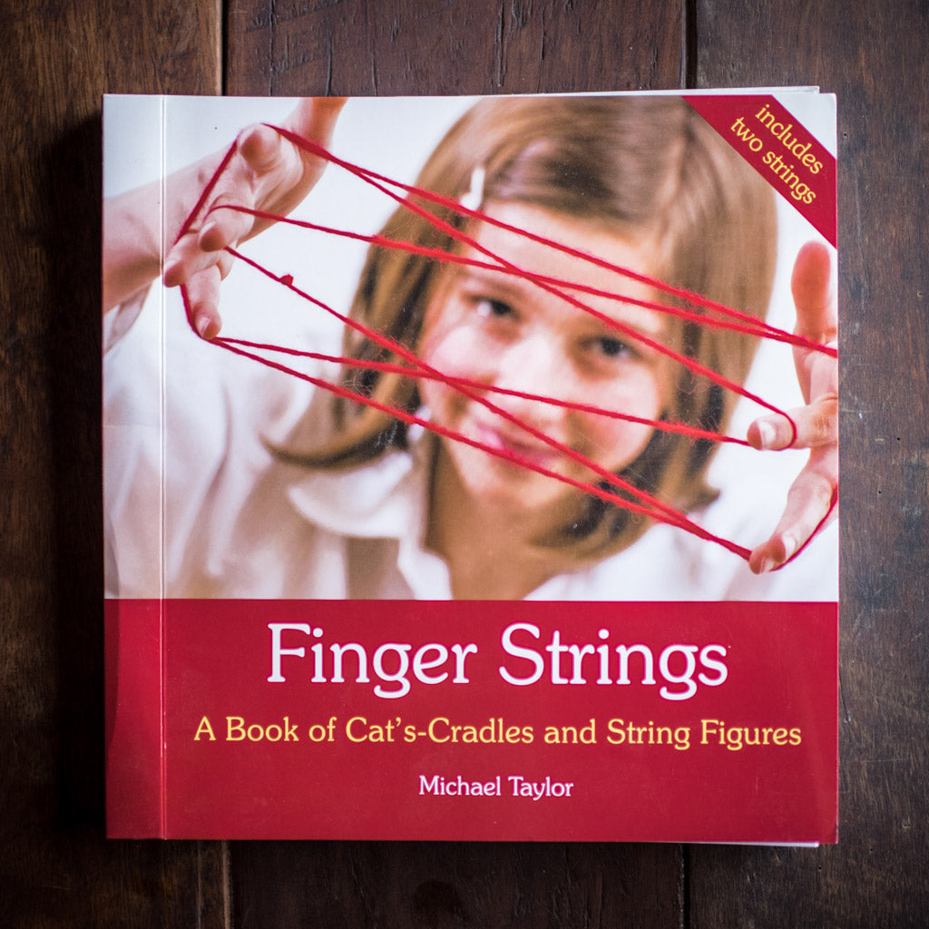 Front cover of Finger Strings book featuring child making cat's cradle.
