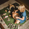 Child sat on a green felt play mat playing with Holztiger wooden animals