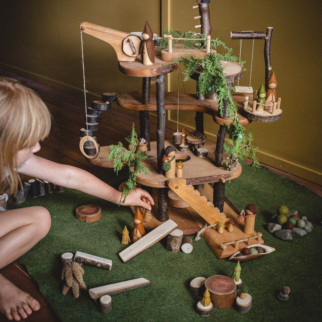 Child sitting and playing with magic wood treehouse with wooden Steiner dolls on large felt mat.