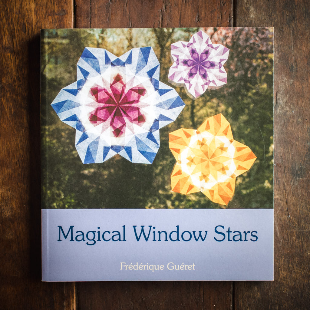 Front cover of Magical Window Stars with waxed kite paper stars on a background of leaves.