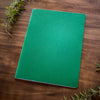 A green Mercurius main lesson book on a wooden backdrop