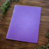 A purple Mercurius main lesson book on a wooden backdrop