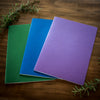 Green, blue, and purple Mercurius main lesson books used for drawing and homeschool on a wooden background