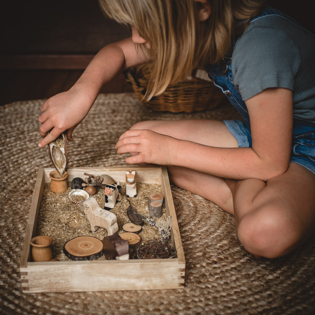child playing with wooden animal toys in tray