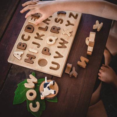 holztiger calf cow on table with child playing with wooden letters