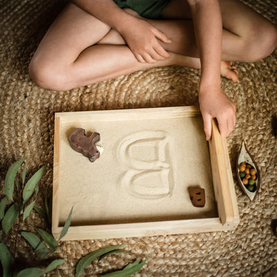 child writing b for bear in sand in a qtoys writing tray for Sweet Elm