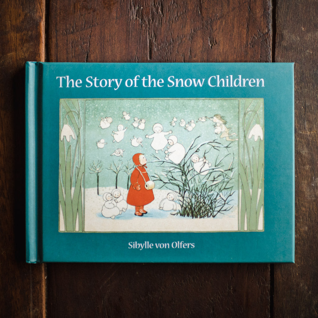 Front cover of The Story of the Snow Children featuring a child in a red cape watching the snow fairies play.