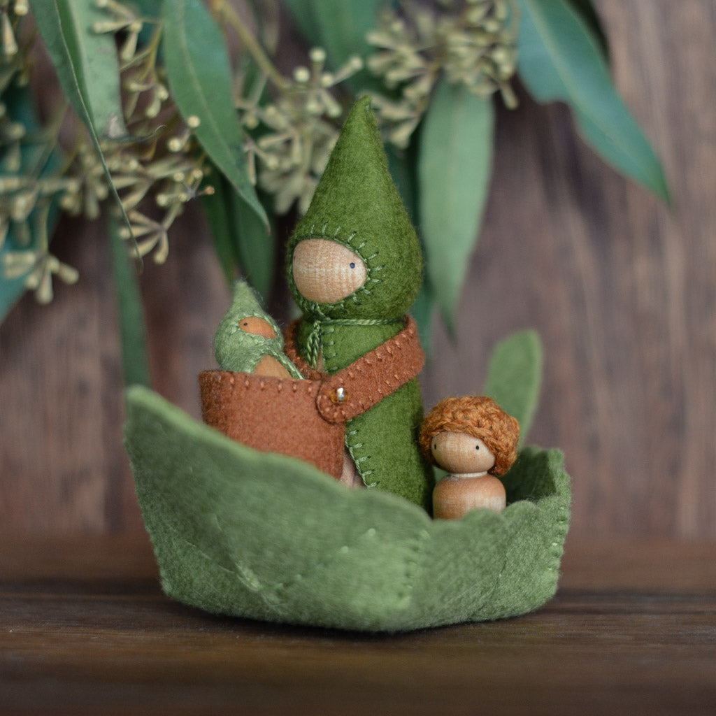 sweet elm leaf boat with dolls laying inside it