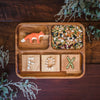 Wooden QToys tray with a Holztiger fox toy and tracing letters filled with beans.