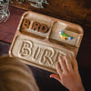 Child spelling the word bird with QToys wooden alphabet letters, sorting tray, and a Holztiger animal.