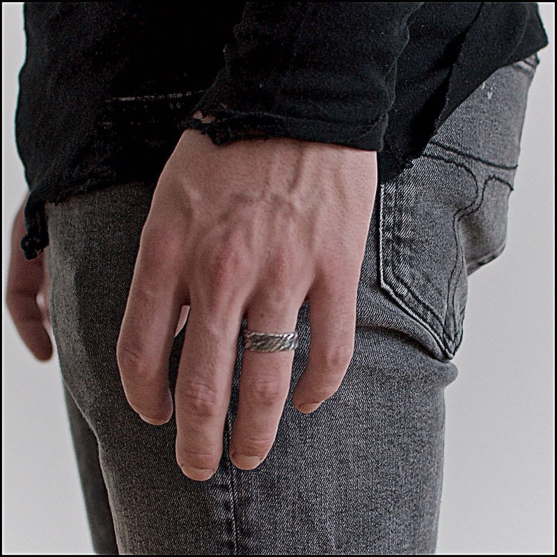 Men's ring Band carved oxid. Shown on male hand model.