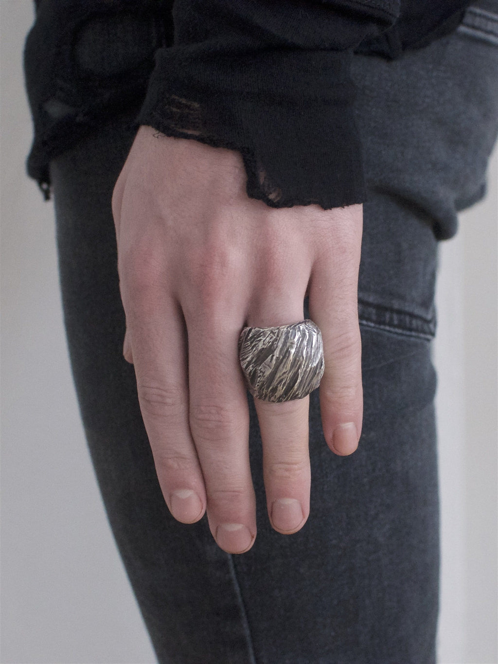 Men's ring Band carved oxid big. Shown on male hand model.
