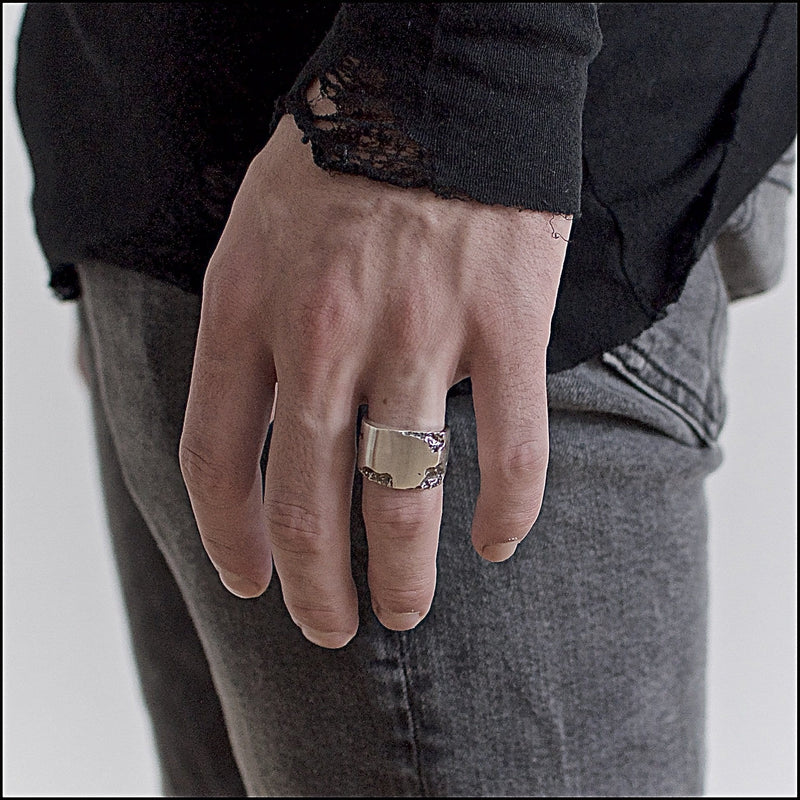 Men's ring Signet eroded. Shown on male hand model.