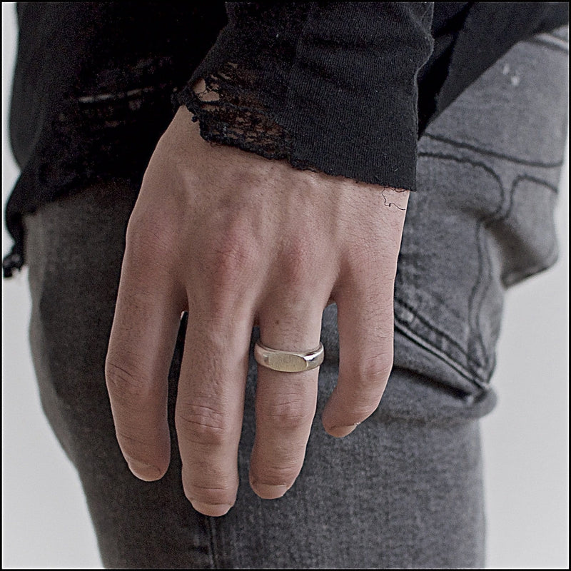 Signet band ring on finger