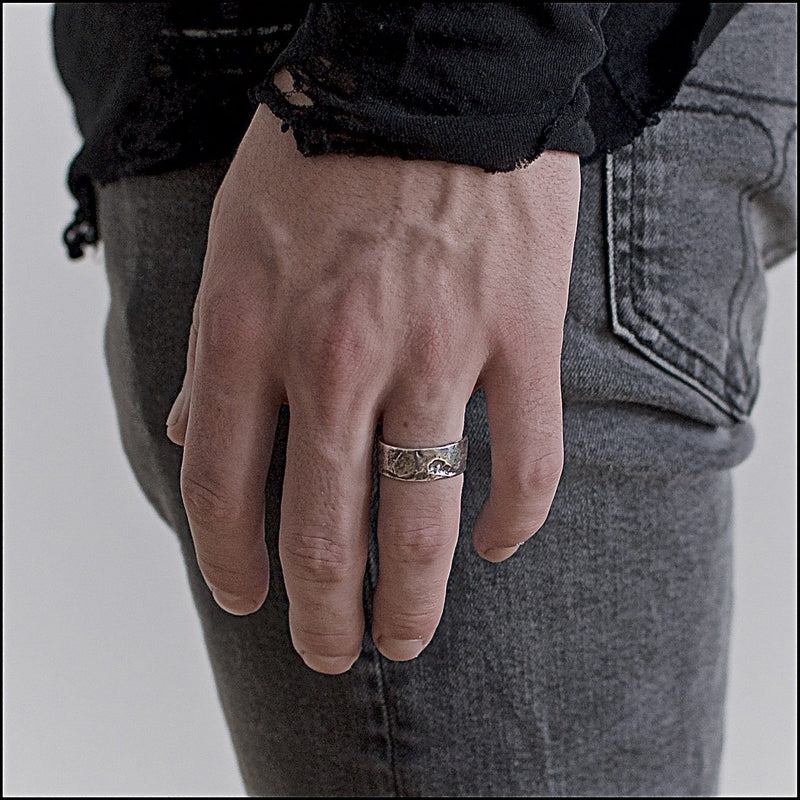 Men's ring Band rock oxid on male hand model.