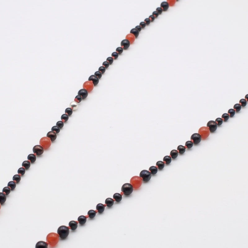 Men´s necklace with freshwater black pearls and red topaz.