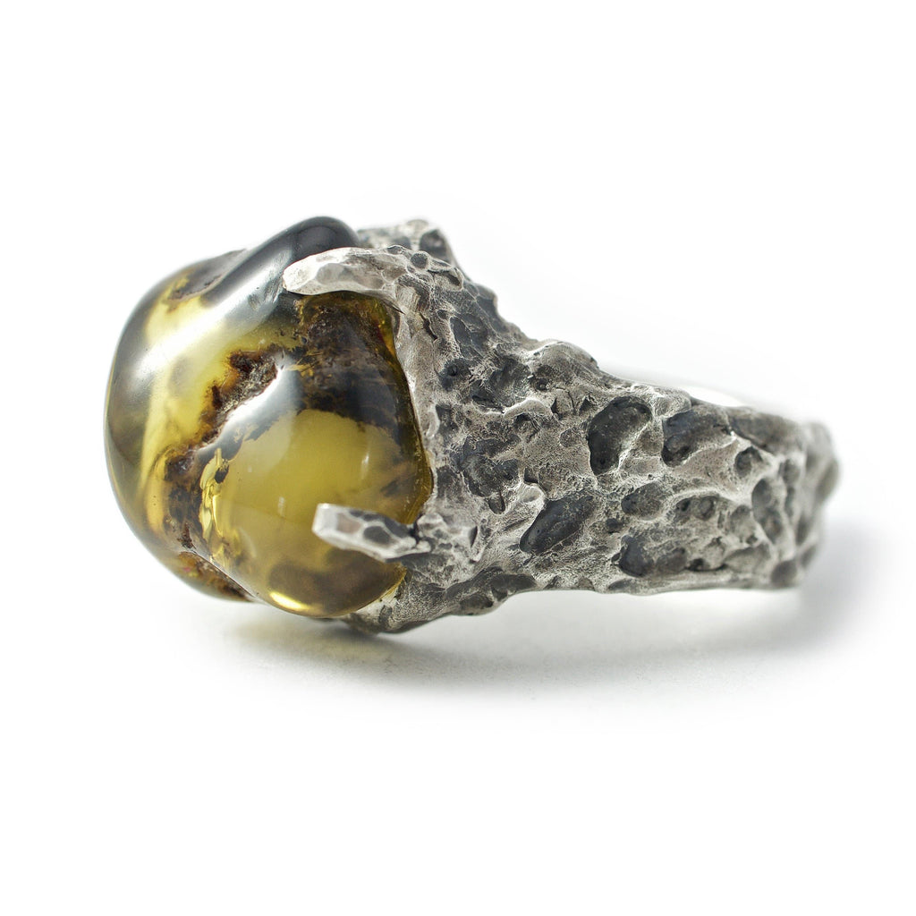 Men's ring Baltic amber green. Side view left. Silver ring with rough surface holding a big amber.