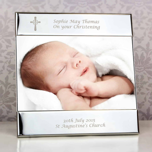 Silver Cross Photo Frame. A silver coloured 6 x 4 photo frame that has a cross in the top left hand corner and can be engraved with 2 messages above the photo and 2 below. a personalised gift for any religious occasion - a wedding, christening, baptism, first communion etc