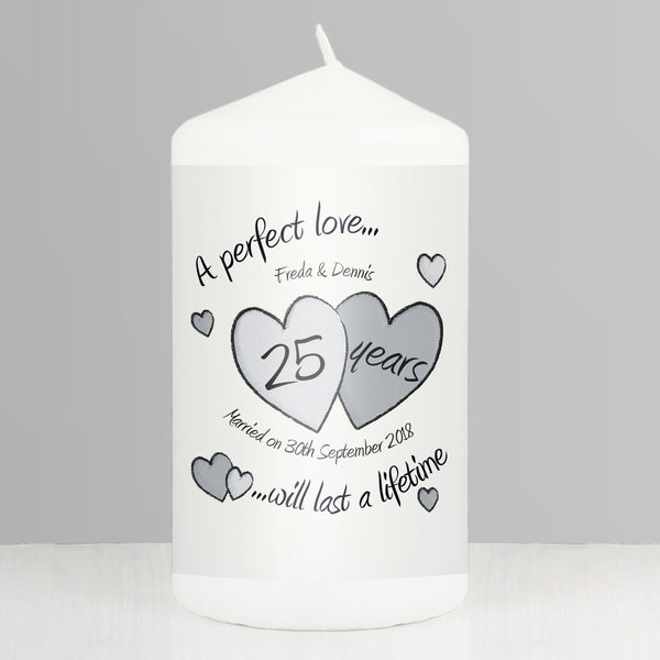 Silver Wedding Anniversary Candle. a white pillar candle that has 2 hearts on the front. it can be personalised with any message over 2 lines which will appear in silver writing. a lovely keepsake for any couple celebrating their silver wedding anniversary.