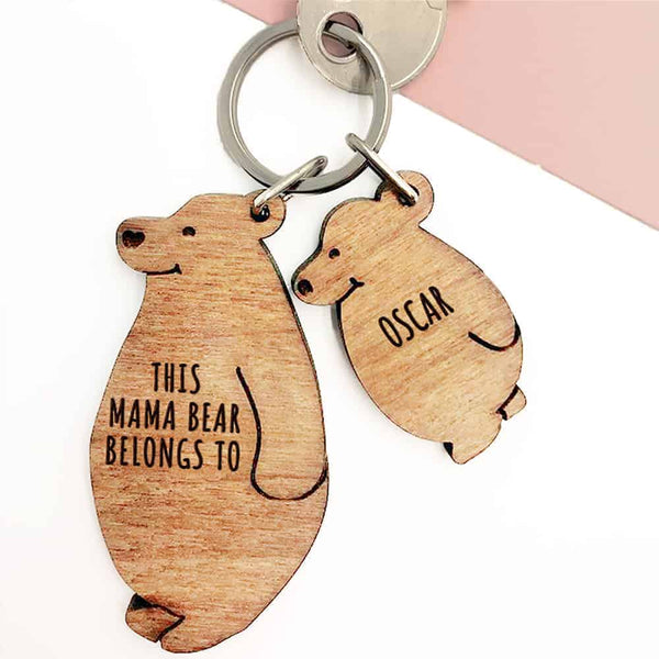 "Mama Bear Keyring Chain Set.  This FSC walnut wood keyring comes in the shape of a smiling, standing bear with ""This mama bear belongs to"" as standard text. You can then add a baby or child bear design for each of your kids. Any name, up to 12 characters, can then be engraved on the cub designs for free! (The child bear is shown as the smaller, upright version of Mama bear; the baby bear faces outward, more oval)."