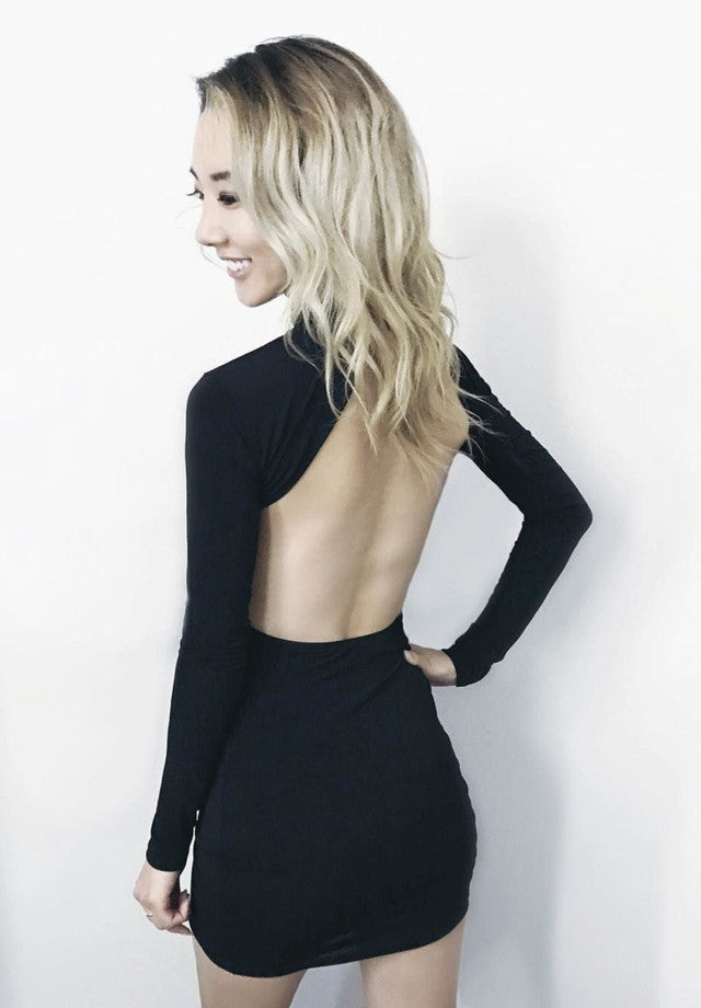 The Kathan backless dress has a figure hugging mini fit, long sleeves, high neck and sassy cut out back.
