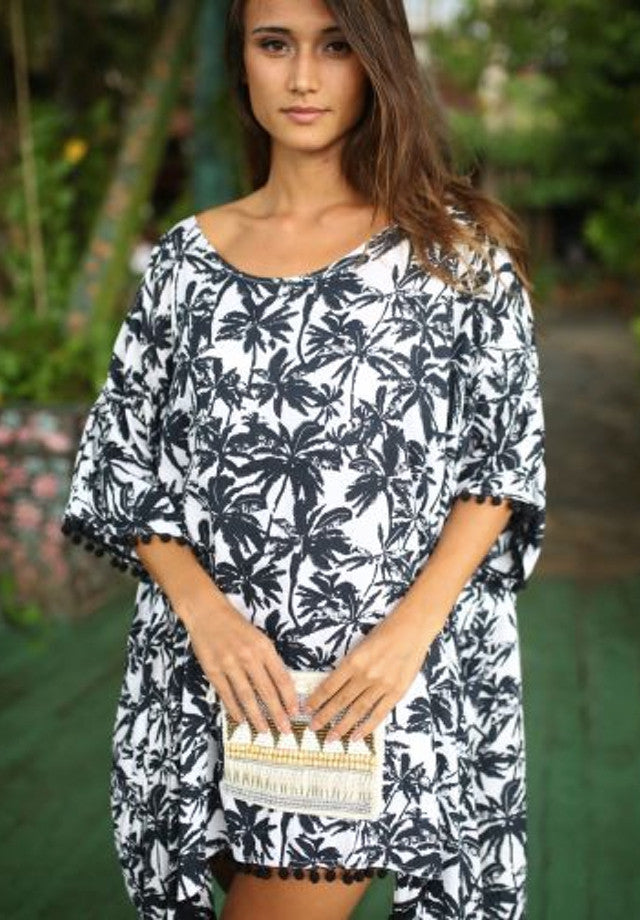 Loose fitting dress with palm tree design and tassels.