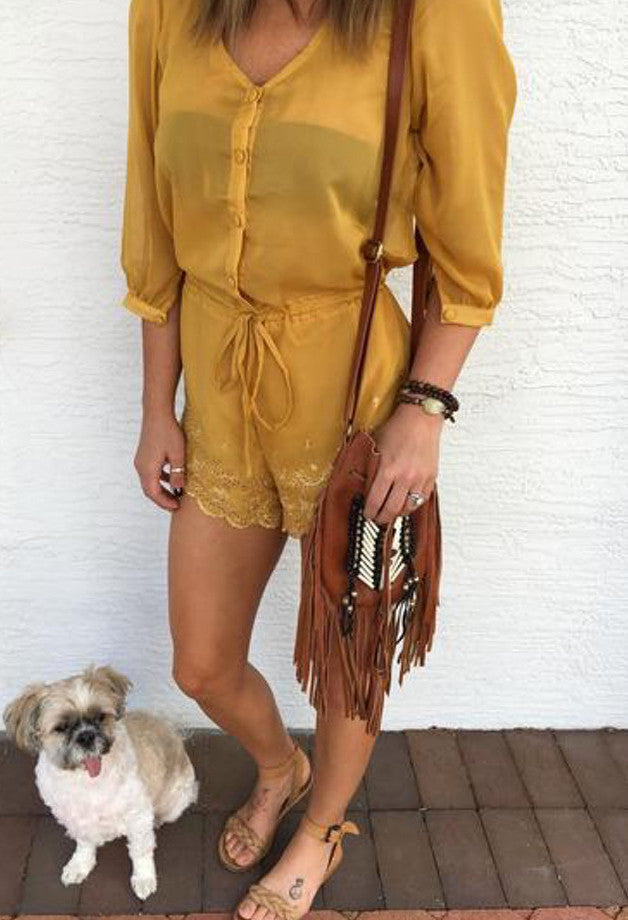 Lioness Goldilocks Romper has button closures, a drawstring waist line, cuff sleeves, a relaxed fit, and scalloped edging.