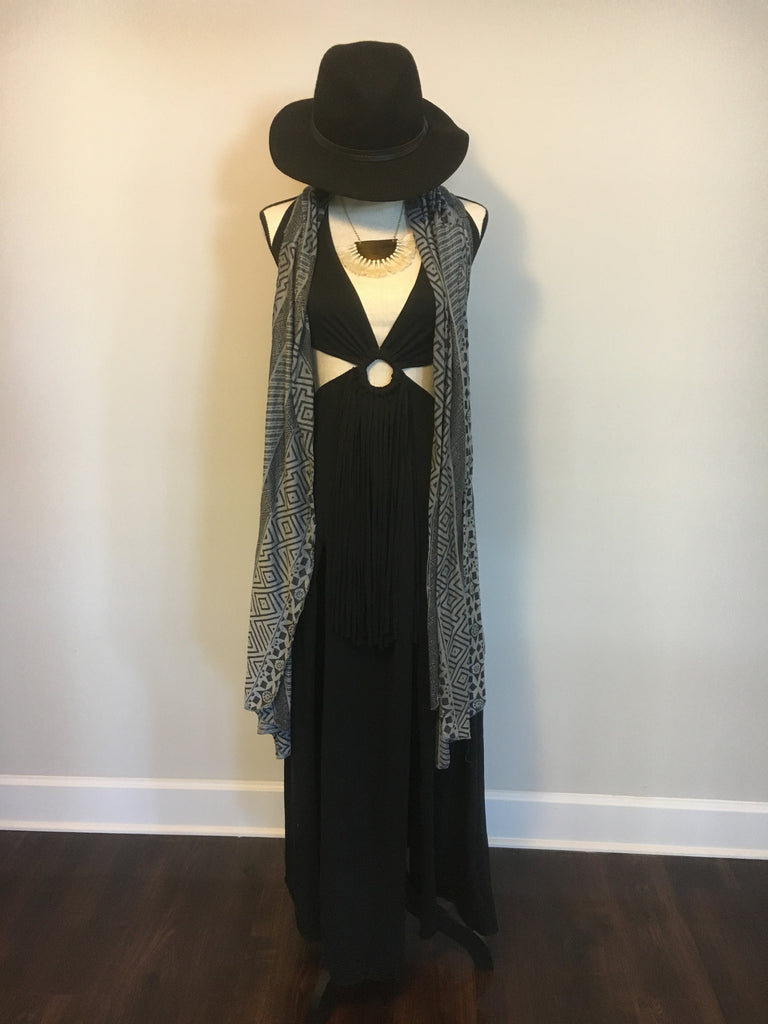 Halter maxi dress with two slits and an open back. Features a wooden ring and raw fringe in the front, elastic at the bust for comfortable fitting and an adjustable halter tie neck so you can somewhat control how deep you want the neckline to be.