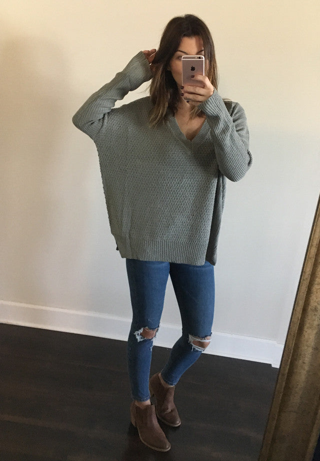 Loose fitting sweater is soft and stretchy loose knit, with pierced details, sweeps across a v-neck into fitted long sleeves.