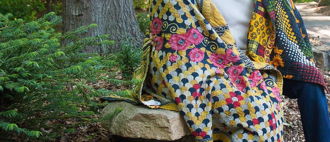 Couple sitting on rock wrapped in Kantha throw by Kantha Home
