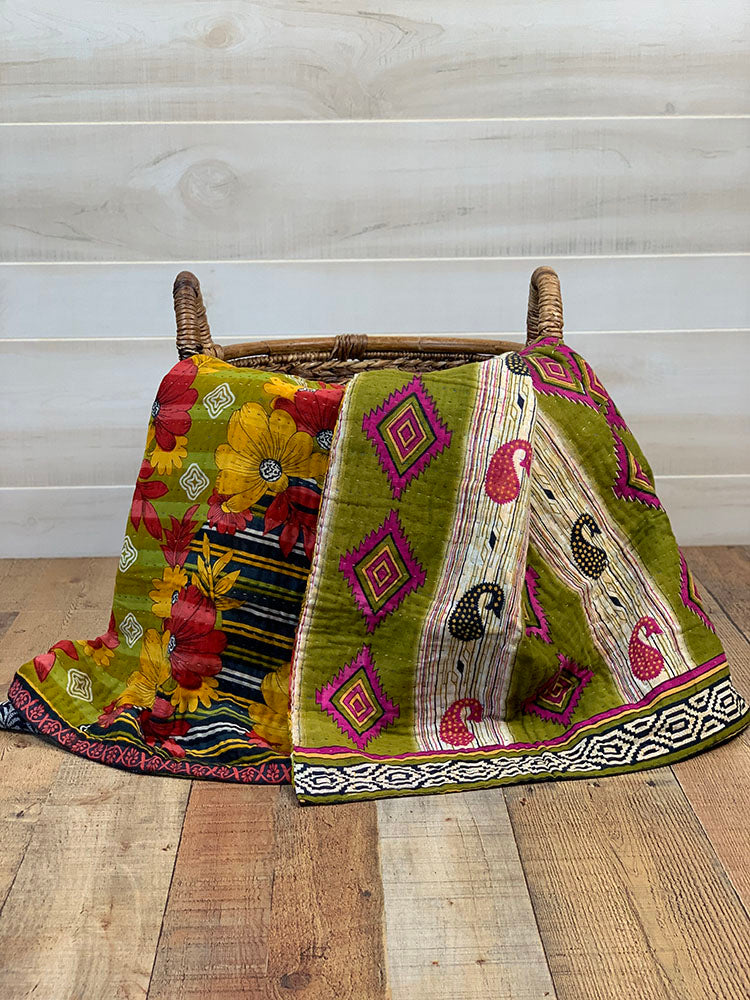 Kantha blanket with navy, green, pink, orange, red, and white colors sit in a basket on wood floor.