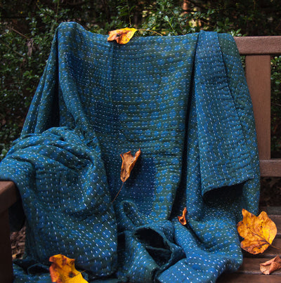 Kantha Home indigo throw in blue green displayed on a bench with leafs around the blanket