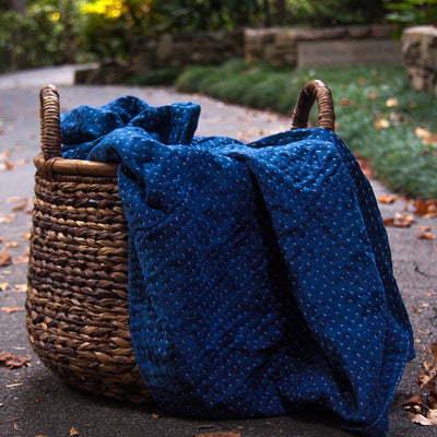 Kantha Home indigo throw in deep blue displayed in a basket