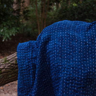 Kantha Home indigo throw in deep blue displayed on a tree branch